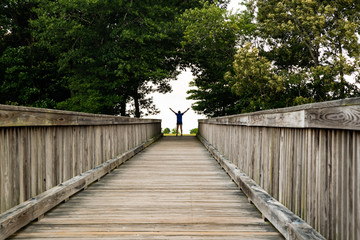 A little girl reaches the end of a long bridge and celebrates in a backlit gap through the trees