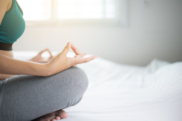 Young woman sitting on bed practicing doing yoga exercise,workout after waking up at home,Healthy and  lifestyle concept,Selective focus
