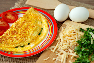 French omelette and its ingredients. French omelette on a bright saucer with an orange pattern. Breakfast of eggs, grated cheese and parsley in colorful tones.