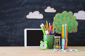Back to school banner. tree of knowledge and pencils in front of classroom blackboard.