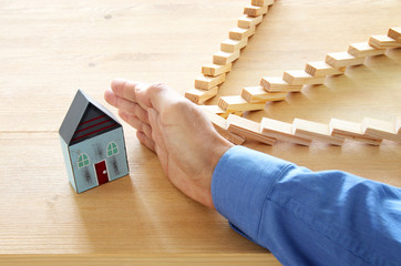 concept image of real estate insurance and protection. man hands blocking the domino effect, saving...
