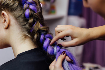 girl in the beauty salon is weaved with braids. braided pigtails.
