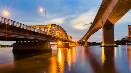 Metal bridge crossing river night view with reflection light