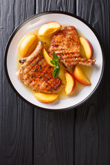 grilled pork chop with glazed peaches and honey garlic sauce close-up on a plate. Vertical top view from above
