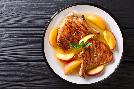 grilled pork chop with glazed peaches and honey garlic sauce close-up on a plate. horizontal top view from above