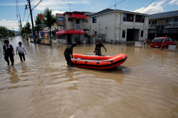 Japan Self-Defense Force soldiers carry a boat for their rescue work at a flooded area in Mabi town in Kurashiki