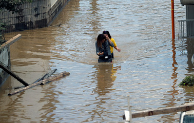 Women make their way through a flooded area in Mabi town in Kurashiki
