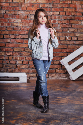 3e3938af8a Hipster girl child wearing white cotton t-shirt, denim jacket,jeans posing  against rough brick wall, minimalist urban clothing style.