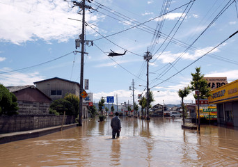 A man makes his way in a flooded area in Mabi town in Kurashiki