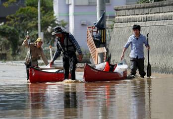 People carry their belongings on canoe in a flooded area in Mabi town in Kurashiki