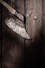 Old broad headed axe with wooden haft on wooden plank background
