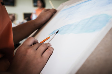 Student's hand with brush drawing on paper for creation picture abstract of watercolor painting with bamboo brush in Art subject classroom secondary education in Thailand