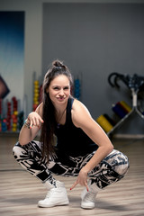 stylish young girl taking a great interest in street dancing, portrait in the gym