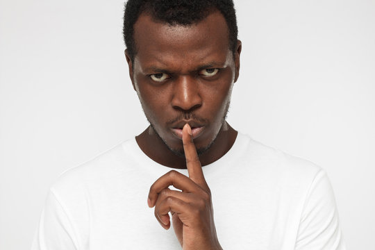 Close up shot of angry african american man with shhh gesture, asking for silence or to be quiet, isolated on gray background