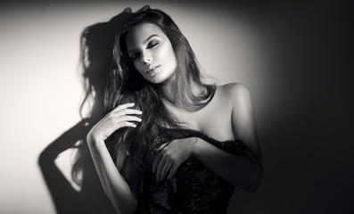 Sexy young woman black and white portrait. Seductive young woman with long hair posing in spotlight