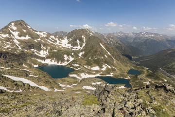 High alpine landscape with snow fields and lakes in the region Ordino Arcalis in the Pyrenees of Andorra