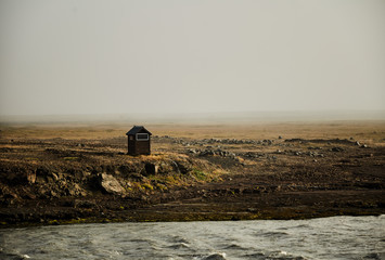 A lonely hut in Iceland. Mountain river on Iceland
