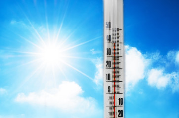 Thermometer against the background of an blue hot glow of clouds and sun, concept of hot weather. Above 40 degrees Celsius.