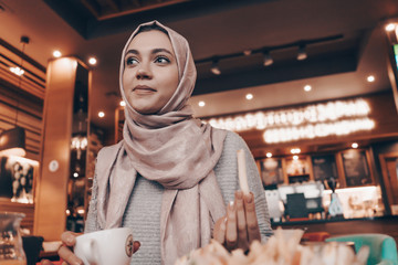A young Arab girl enjoys a delicious meal in a restaurant, thinks about something