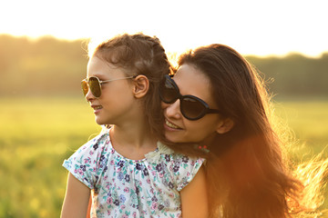 Happy fashion kid girl and her mother in trendy sunglasses on nature bright sunset background. Closeup portrait of happiness.