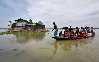 Flood affected villagers are transported on a boat towards a safer place at a village in Morigaon district