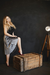 Beautiful and fashionable blonde model girl with big breast in silver skirt, in black satin blouse and dark-red shoes, stands on a wooden chest, smiling and posing in studio at dark interior