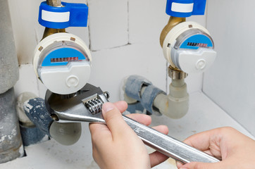 Technician installs a new water meter with wrench