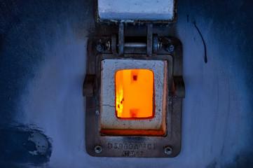 Vue sur le foyer du four de la chaudière avec la porte ouverte d'une usine chimique en format paysage