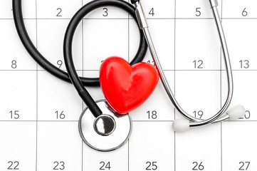 Calendar with stethoscope and red heart. Date for medical examining. Top view.