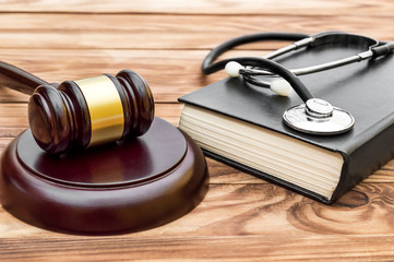 Gavel with stethoscope and book on the table.