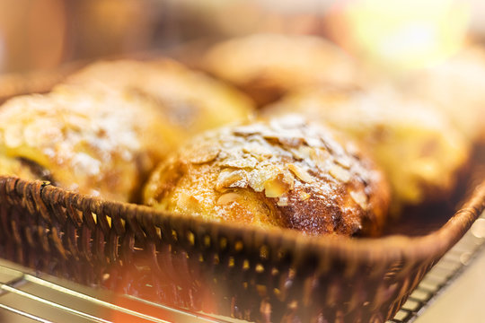 French almond chocolate croissant in bamboo woven basket, selective focus and lens flare