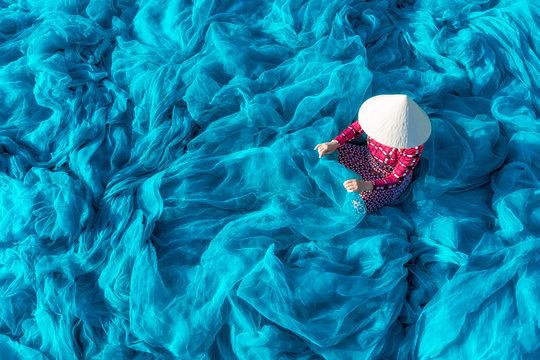 Vietnamese woman repair fishing net