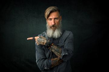 Porträt eines bärtigen Geschäftsmannes, der mit seinem Finger Richtung rechte Seite zeigt, stehend vor schwarzem  Hintergrund