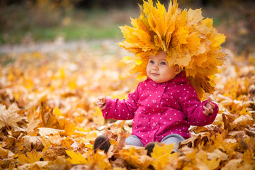 Little kid is playing and sitting in fallen leaves in autumn park. Baby is in big wreath of leaves....