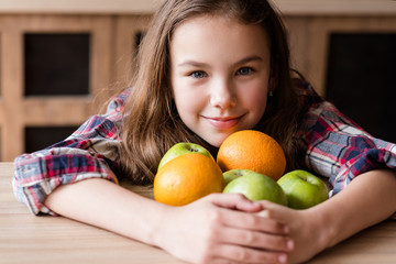 balanced child nutrition. organic fruit for health wellness and fitness of youngsters. girl holding a mix of oranges and apples in hands