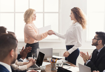 Boss handshaking employee congratulating with promotion
