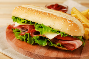 Fresh submarine sandwich with ham, cheese, bacon, tomatoes and  lettuce on wooden cutting board