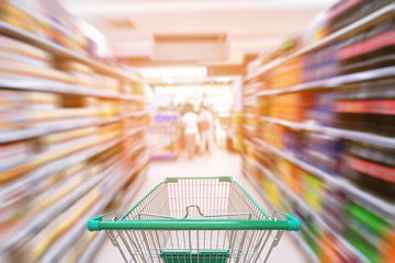 Shopping trolley in department store with goods shelf background, Abstract motion blurred concept