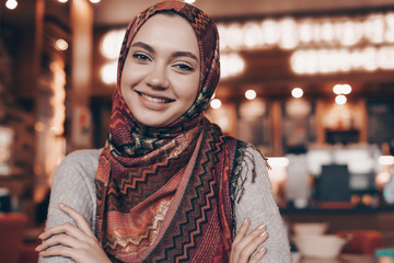 cute charming arabic girl with a headscarf on her head looking at the camera and smiling sits in a cafe