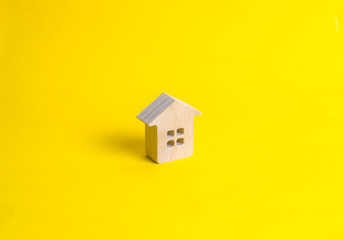 A small wooden house stands on a yellow background. The concept of buying and selling real estate, renting. Search for a house. Affordable housing, credit and loans. Investments in business