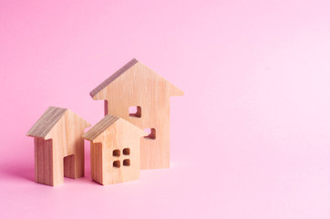 Three houses on a pink background. Buying and selling of real estate, construction. Apartments and apartments. City, settlement. Minimalism. for presentations. real estate market.