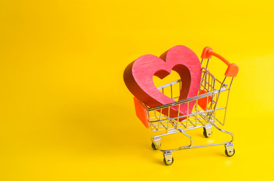 A supermarket trolley with a red heart inside. Love of shopping and shopping. Favorite store or supermarket. Buy love and happiness. Shopaholics, consumer society. Intimate services for money