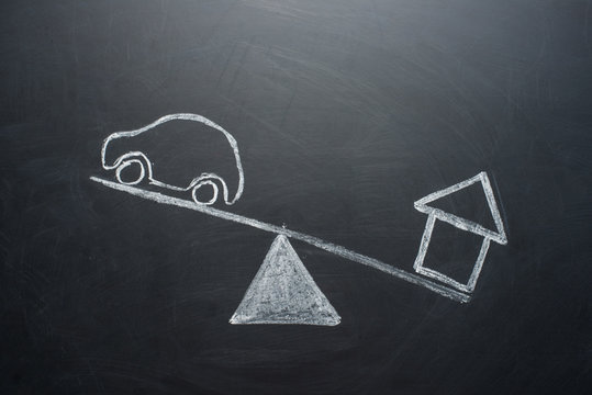 Car and the house on the scales. The concept of choice between home and credit, financial problems