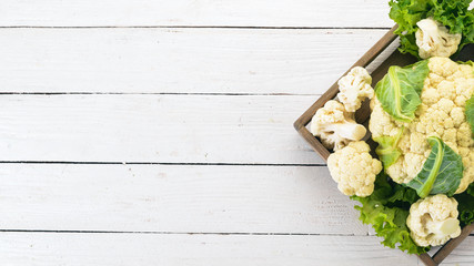 Cauliflower in a wooden box. Fresh vegetables. On a wooden background. Top view. Copy space. Fototapete