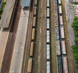 Cargo wagons on train station in city, aerial view
