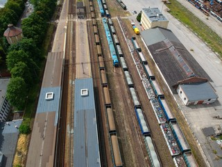 Cargo and passenger wagons on train station in city, aerial view