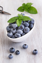 Drops fresh blueberries in a white bowl, with meant leaves on a wooden background