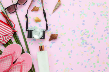 Flat lay objects the accessory for travel summer holiday background concept.Table top view of fashion clothing to traveler at beach.Sun block protection lotion with items on modern pink paper.