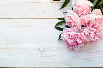 Peonies on a white wooden background with copy space