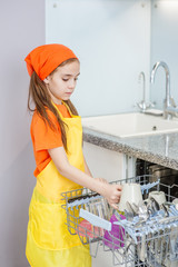 Little girl using a dishwasher in a modern kitchen. domestic appliance
